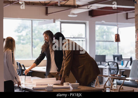 Gente de negocios discutiendo anteproyectos en la oficina
