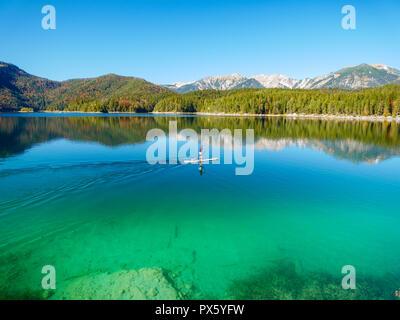 Imagen del stand up remando en un hermoso lago de montaña en otoño
