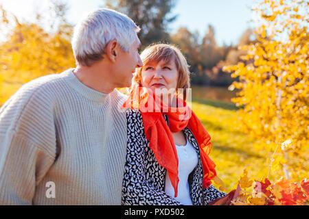Las parejas ancianas caminar en otoño del bosque. Hombre de mediana edad y la mujer abrazándolo y escalofriante al aire libre. Gente hablando y disfrutar de la naturaleza