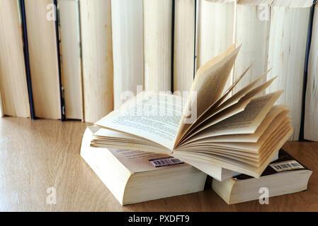 Fila de libros antiguos libro abierto en la parte delantera. Foto de stock