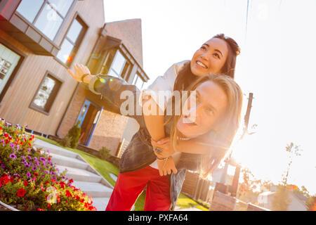 Feliz pareja positiva de pie en frente de su casa Foto de stock