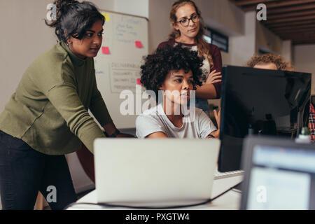 Los ingenieros de software que trabajan en el proyecto y la programación en la compañía. Inicio grupo de negocios trabajar como equipo para encontrar una solución al problema. Programador de mujer