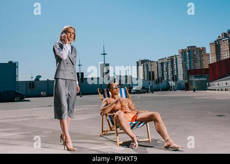 Joven atractivo relajarse en las hamacas mientras que su señora boss en traje junto a él, y hablando por teléfono sobre el estacionamiento