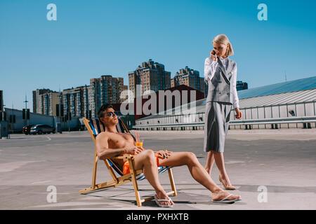 Apuesto joven relajarse en las hamacas mientras que su señora boss en traje junto a él, y hablando por teléfono sobre el estacionamiento