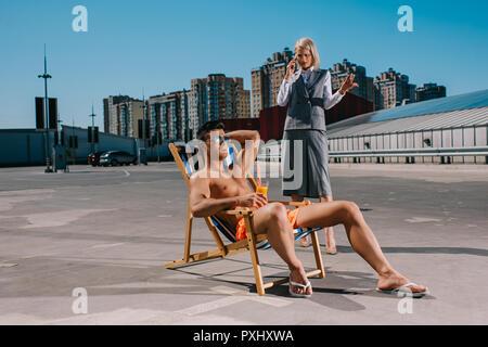 Apuesto joven relajarse en las hamacas mientras su loca lady boss en traje de pie junto a él, y hablando por teléfono sobre el estacionamiento