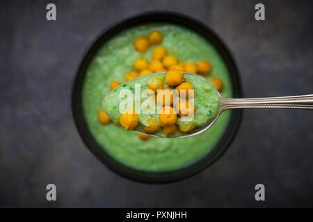 Tazón de gazpacho verde con aguacate y cúrcuma garbanzos tostados, de cuchara, close-up