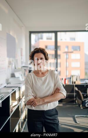Empresaria exitosa en su oficina de pie con los brazos cruzados Foto de stock
