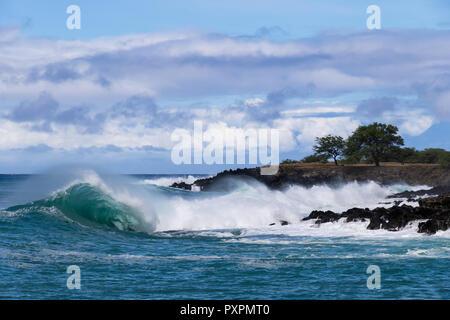 Onda de curling cresterías y arrastrando el rocío del mar, como se rompe cerca de la costa de la costa de Kona en la Gran Isla de Hawaii.