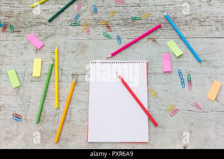 Cuaderno espiral, clip para papel, marcadores y lápices de colores sobre madera