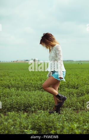Mujer joven caminando por un campo verde