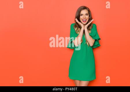 Emocionada bella joven en mini vestido verde está manteniendo la cabeza entre las manos, mirando a la cámara y gritando. Tres cuartos de longitud studio shot sobre naranja