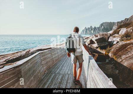 Hombre caminando por la playa turística puente de madera con mochila viajando en Noruega heathy concepto de aventura en el estilo de vida al aire libre vacaciones
