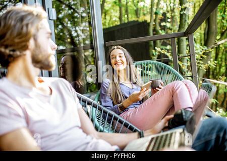 Un hombre y una mujer joven con un ordenador portátil y teléfono relajante sentarse en el balcón en el hermoso bosque