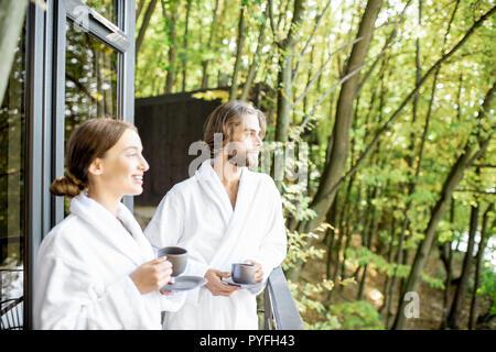Pareja joven en batas de baño disfrutando la naturaleza de pie con el café en la terraza en el hermoso bosque verde