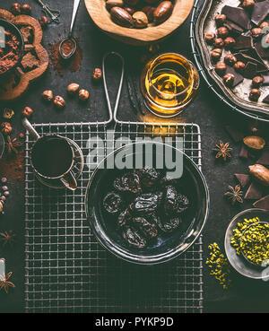 Empapado en ron ciruelas pralines caseras con diversas especias, chocolate y nueces ingredientes sobre fondo de tabla oscura con utensilios de cocina, vintage