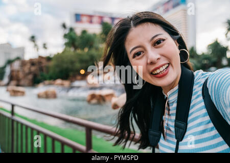 Cute lady teniendo selfie delante del estanque en el parque en América. joven viajar de forma independiente en las vegas. mujer toma auto portrairt con foto Foto de stock