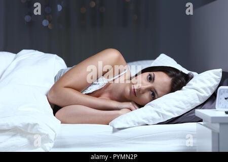 Insomniac grave mujer mirando a la cámara tumbado en la cama en la noche en su domicilio.
