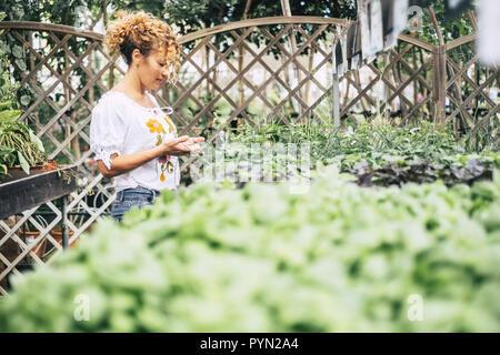 La mujer joven en un invernadero con muchas plántulas admira el crecimiento de flores blancas como margaritas. Concepto de cuidado y pasión por la naturaleza. Nature s
