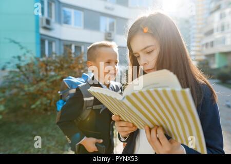 Retrato al aire libre de la sonrisa de escolares en la escuela primaria. Un grupo de chicos con mochilas se divierten, hablando. La educación, la amistad, techno Foto de stock