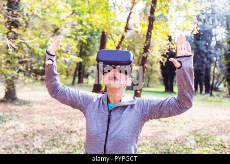 Sorprendido mujer mayor diversión con casco de realidad virtual en el bosque, VR dispositivo con ancianos.