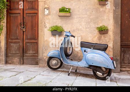 Scooter aparcado por una puerta de madera en Lovere en lago de Iseo, Italia
