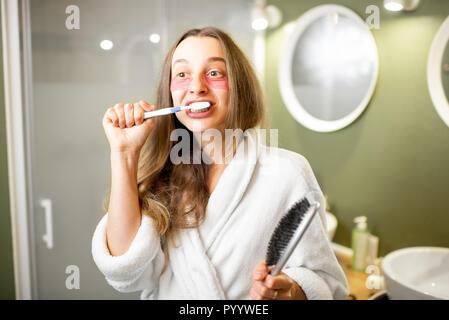 Joven y bella mujer en albornoz cepillando sus dientes en el cuarto de baño