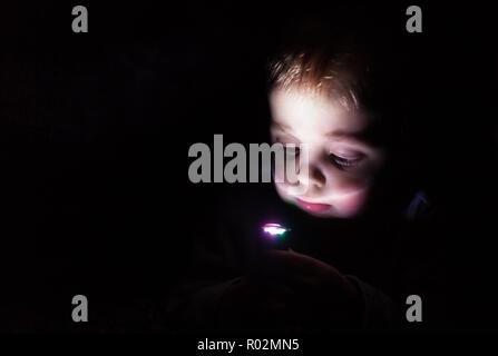 Little Boy caucásica jugando con la pequeña linterna en un cuarto oscuro en casa