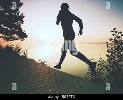 Congela la acción shot de tall ejecutando deportista llevar zapatillas de moda y ropa deportiva el ejercicio de mañana en la orilla. Pista de pavimento alrededor del lago.