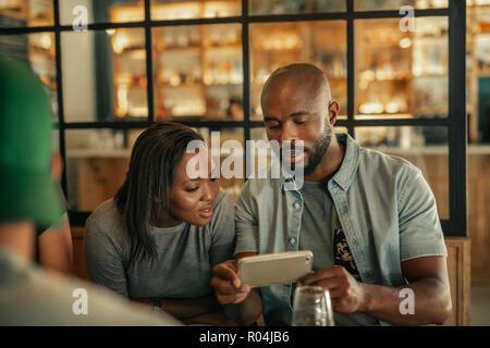 Dos amigos sentado en un bar mirando fotos movil