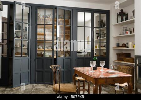 Mesa y sillas con almacenaje de cocina en el fondo, Bretaña