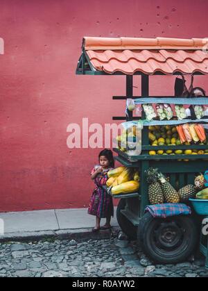 Pequeña niña guatemalteca joven en la vestimenta maya escondido detrás de su familia cesta de frutas parada callejera