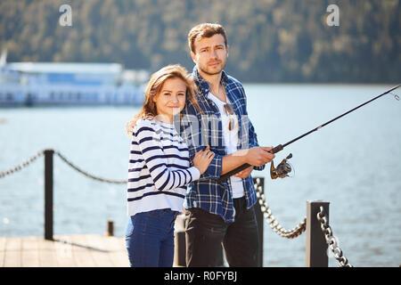 Pareja joven tranquila con un estanque de pesca en otoño en el lago