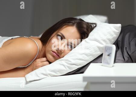Sleepless insomniac chica mirando el despertador tumbado en la cama en la noche en su domicilio.