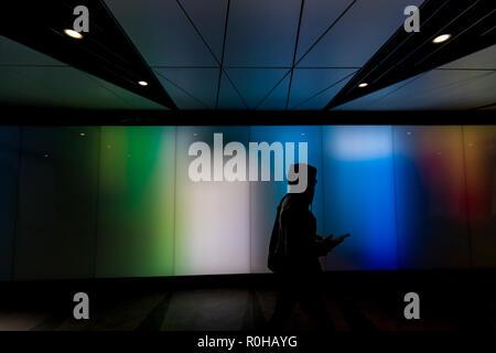 Joven caminar utilizando el teléfono en moderno futurista sci-fi moody oscuro túnel en la ciudad de Londres luces de fondo