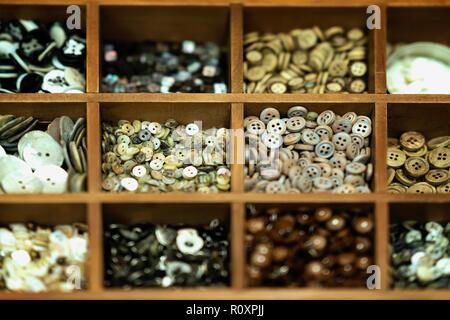 Distintos botones multicolores en cajas de madera para la creatividad, una verdadera tienda, selectiva de fondo. La industria textil, la confección, aficiones, handmade
