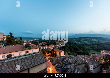 En Chiusi niebla niebla de noche, tarde o mañana en Umbría, Italia, cerca de Toscana, iluminado con luces en las calles, casas de la azotea en la montaña campo, r