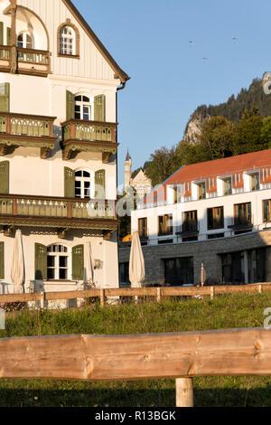 Schwangau, Baviera, Alemania, 2018. Restaurante Alpenrose am See, el hotel recientemente construido y el castillo de Neuschwanstein en una soleada tarde de finales de septiembre.