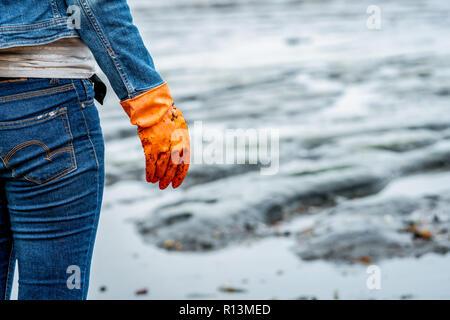 Un hombre con guantes naranjas recogiendo basura en una