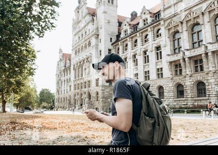 Un turista hombre o niño con una mochila o un estudiante en Leipzig en Alemania utiliza un teléfono móvil para ver un mapa o una llamada o para otra. Foto de stock