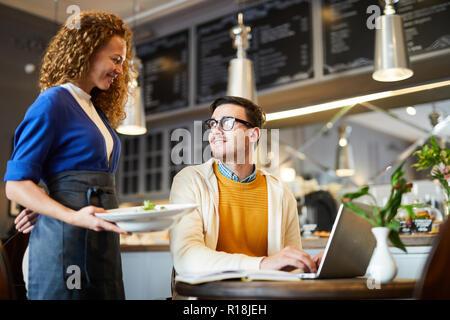 Joven camarera traer el orden a uno de los clientes sentados por tabla y redes