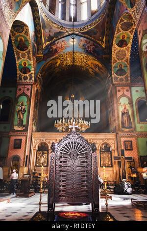 Interior de la preciosa iglesia ortodoxa en el país de Georgia con la mujer orando en el fondo Foto de stock