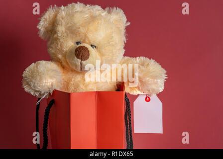 Cerrar con un oso de peluche juguete con una etiqueta de venta en blanco en su brazo, metidas en una bolsa de papel comercial contra un fondo de color rojo