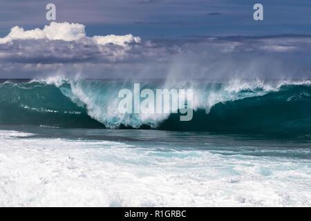 Ola enrollan en playa hawaiana, a punto de estrellarse en el agua por debajo. Volver a rociar flyng superior del wave. South Point. Mar Blanco spray lanzados al aire.