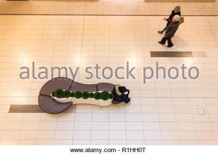 Conectado pero solas debido a la tecnología de dispositivo de teléfono inteligente y las relaciones en el centro comercial en Canadá Foto de stock