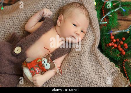 Hermoso bebé recién nacido acostado sobre una manta vista desde la parte superior.