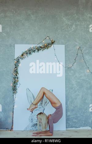 Vista lateral retrato de mujer joven con slim hermoso tatuaje en su pie en el trabajo, hacer yoga o pilates ejercicio. Scorpion, vrischikasana pose. Fu
