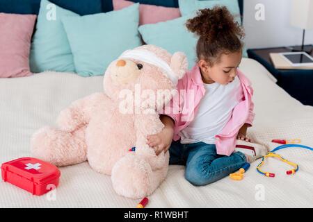 Pequeño niño africano-americanos en rosa chaqueta jugando al doctor con osito de peluche
