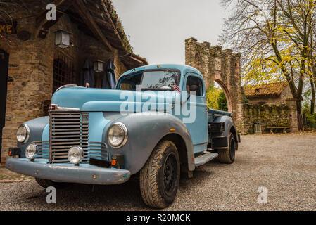 Histórico del recogedor de color azul, estacionado en las calles de un histórico pueblo italiano, coches clásicos americanos, imagen horizontal