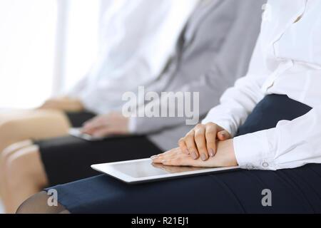Gente de negocios esperando para entrevistas de trabajo o tomar parte en la conferencia en la oficina, cerca. Las mujeres sentadas en sillas como en cola o reunión