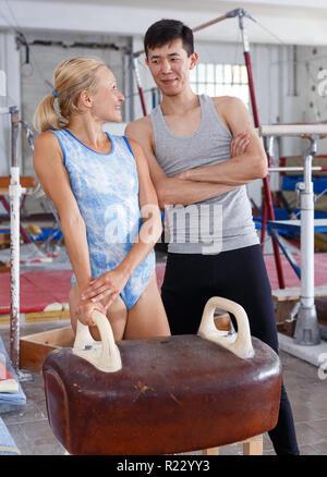 Colocar par hombre y mujer posando cerca de equipos de gimnasia en el gimnasio Foto de stock